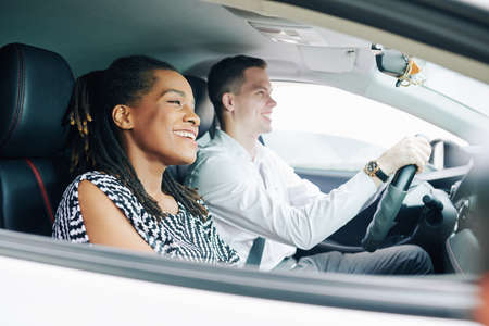 Happy African woman sitting in the passesnger seat and smiling while her boyfriend driving a car Stock Photo - 130125449