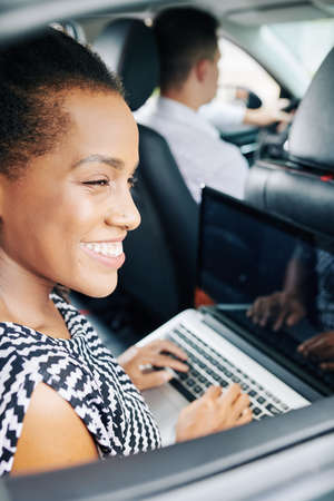Happy African woman working on laptop computer while driving in car as a passenger Stock Photo - 130125464