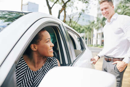 African smiling woman sitting in a car and suggesting the young man to drive him