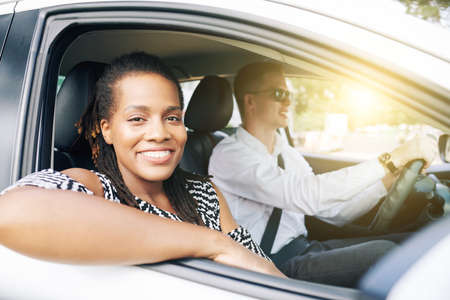 Portrait of African woman smiling at camera while sitting on passenger seat in car together with young man Фото со стока