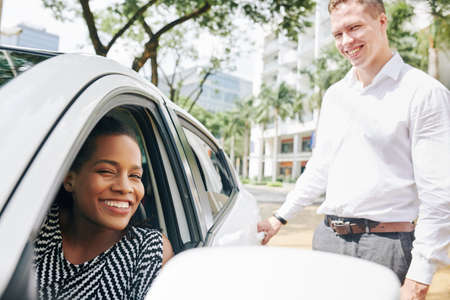Portrait of African young woman smiling at camera while sitting in the car with young man opening the back door of the car Stock Photo - 130125341