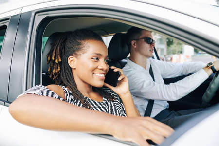 Happy African woman smiling and talking on mobile phone while travelling by car with man sitting near her and holding the wheel Stock Photo - 130125344