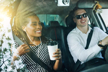 African young woman drinking coffee smiling and talking to young man while he driving a car