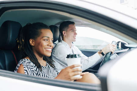 Happy African girl drinking coffee and smiling while sitting in the car with young man