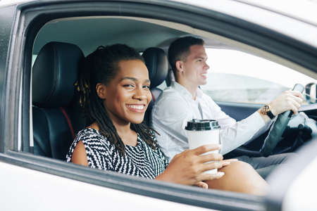 Afrikanische junge Frau lächelt in die Kamera, während sie während ihrer Fahrt mit dem Auto zusammen mit einem jungen Mann Kaffee trinkt