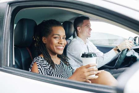 Giovane donna africana che sorride alla macchina fotografica mentre beve caffè durante il suo viaggio in auto insieme a un giovane uomo