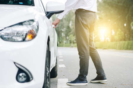 Close-up of young man opening the door of white car and he is going to sit down in it Stock Photo