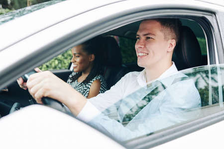 Young smiling man holding the wheel and driving a car with female passenger sitting near by him Stock Photo - 130125358