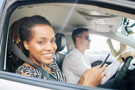 Portrait of African young woman smiling at camera and using mobile phone with young driver driving the car Stock Photo - 130125302