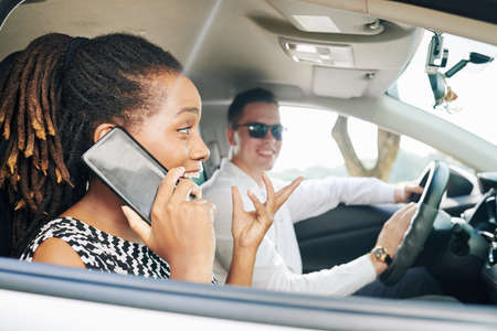 Excited African woman talking on mobile phone and gesturing with young man in sunglasses sitting behind the wheel and driving a car