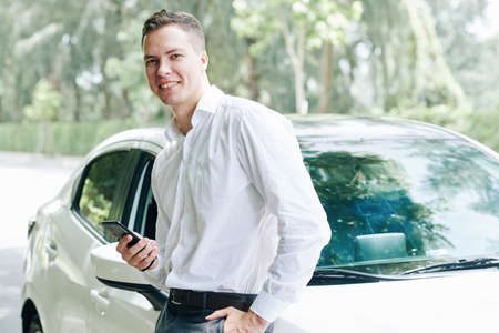 Portrait of young man holding mobile phone standing near his car and smiling at camera outdoors