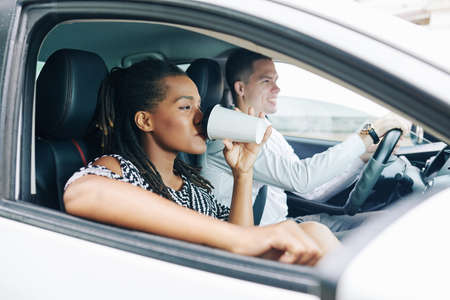 African young woman drinking coffee while sitting on passesnger seat with young man who driving a car Stock Photo - 130125334