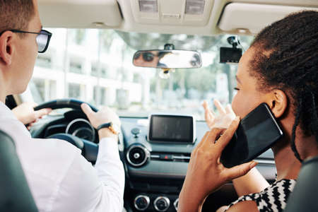Rear view of multiethnic couple sitting in the car young man driving and woman talking on mobile phone