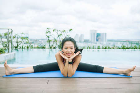 Portrait of happy Asian woman sitting on exercise mat and smiling at camera during training outdoors with swimming pool in the background