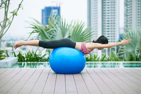 Young sporty woman lying on fitness ball and stretching her legs and hands during sports training near the poolside outdoors with modern buildings