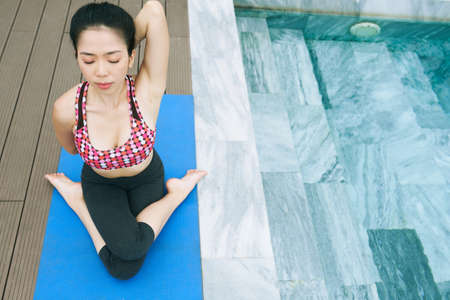 Asian healthy woman sitting on exercise mat with her eyes closed and stretching during yoga outdoors