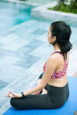 Asian young woman sitting on exercise mat in lotus position and with her eyes closed and doing breathing exercise in front of the swimming pool