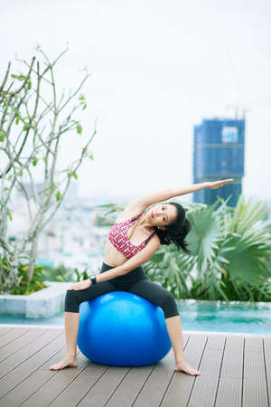 Portrait of Asian young woman looking at camera while sitting on fitness ball and doing stretching exercises outdoors 版權商用圖片