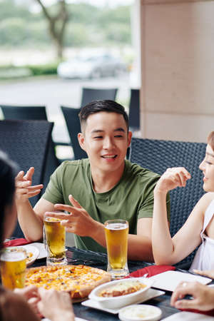 Asian young man talking to his friends while they have dinner at the restaurant together they eat pizza and drinking beer