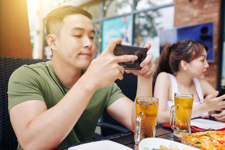 Asian young man using his mobile phone and typing a meesage while has a dinner with his friends at the table in cafe Reklamní fotografie