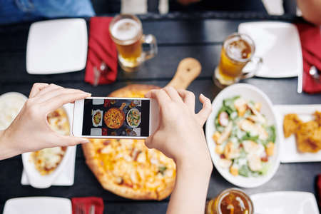 Close-up of man holding mobile phone in his hands and making a photo of his dinner while sitting at the cafe Stock Photo