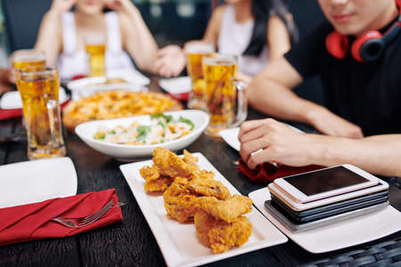 Close-up of fried chicken and mobile phones are on the wooden table with people having dinner in the background in cafe Stok Fotoğraf