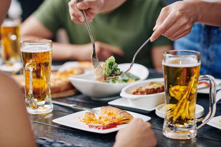 Close-up of woman taking salad with spoons from the bowl while have dinner together with her friends they drinking beer during dinner