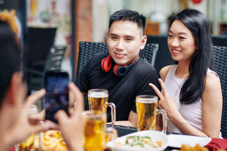Asian young couple smiling and posing at camera of mobile phone while sitting at the table together with their friends in restaurant