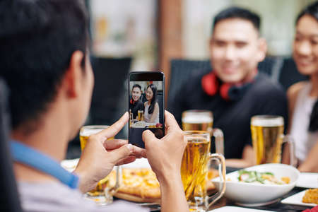 Rear view of young man making a photo of his friends on his mobile phone while they have dinner at the restaurant