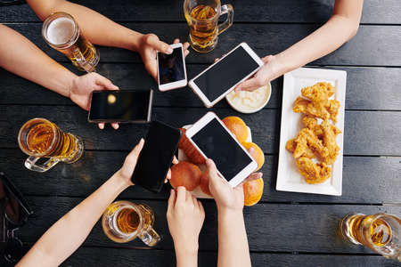 High angle view of friends holding mobile phones and connecting them with each other during their meeting in the bar