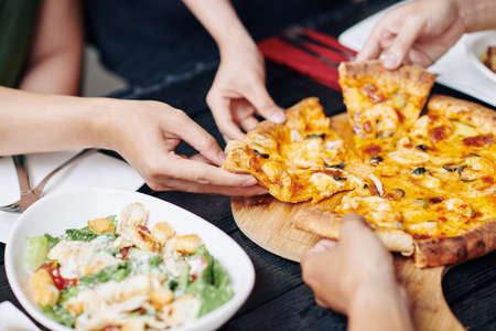 Close-up of people taking slices of pizza from the table and eating them during lunch in cafe