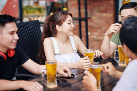 Group of young Asian friends sitting at the table with glasses of beer and talking to each other in outdoor cafe