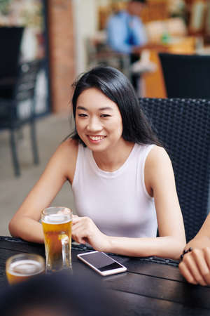 Happy Asian young woman sitting at the table and smiling while drinking beer in outdoor cafe