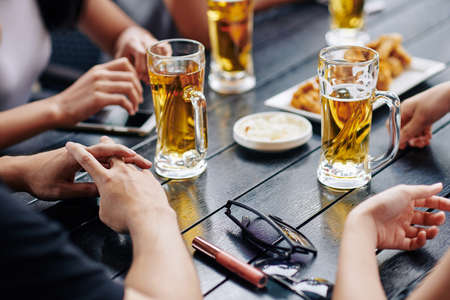 Close-up of young people sitting at the table and drinking beer from the glasses in the bar Stock fotó