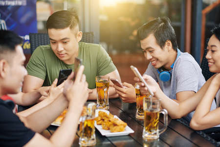 Group of Asian friends communicating online using their mobile phones while they sitting in cafe and drinking beer Reklamní fotografie