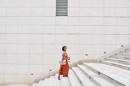 African happy woman in elegant orange dress holding coffee drink and moving up the stairs in the city Stock fotó