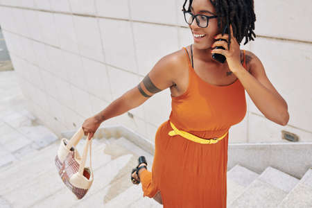 African stylish woman in bright orange dress and in eyeglasses talking on her mobile phone while moving up the stairs outdoors