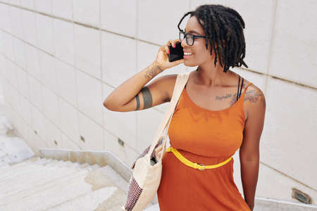 African smiling woman in elegant orange dress has a conversation on mobile phone while standing outdoors in the city