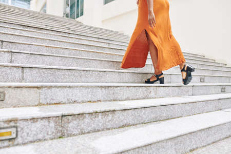 Close-up of young woman in orange long dress moving up the stairs in the city