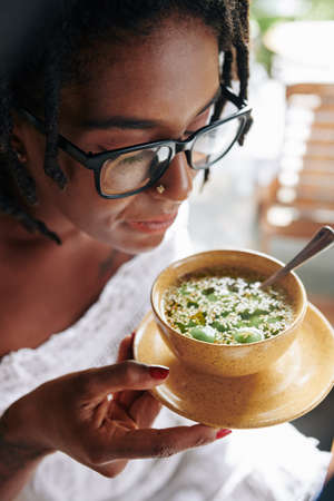 African beautiful woman in eyeglasses holding bowl with exotic food and tasting it