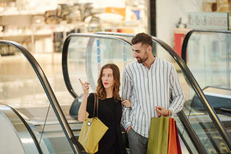Pretty young woman pointing at boutique in shopping mall when standing on escalator with her husband Фото со стока