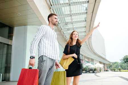 Smiling young woman making hand gesture to catch taxi when her husband standing near by with shopping bags