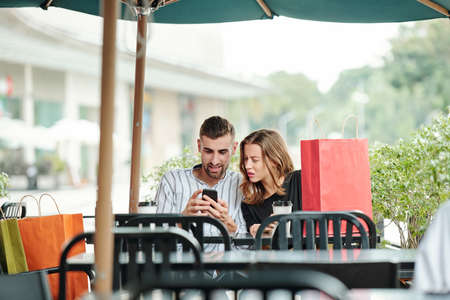Frowning young woman looking at screen of smartphone in hands of her boyfriend when they are sitting at cafe table after shopping