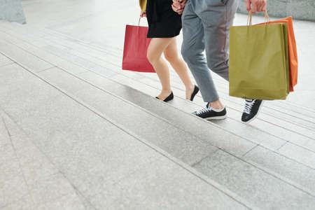 Cropped image of young people with paper-bags hurrying to sale in mall on Black Friday