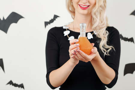 Bottle of orange poisonous magic potion in hands of smiling witch