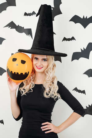Portrait of confident pretty young woman in sorceress costume showing orange balloon with painted eyes and scary toothy smile