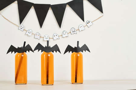 Decorated cocktail bottles with paper bats attached to straws at Halloween party