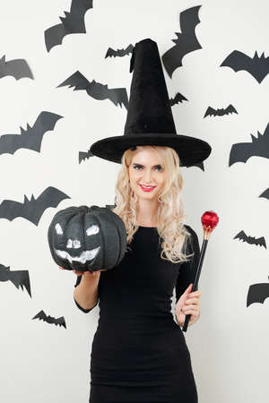 Slim young beautiful sorceress posing with black Halloween pumpkin and magic wand against wall with black bats