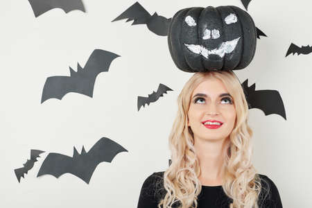 Cheerful young woman smiling and looking up at black painted pumpkin on her head