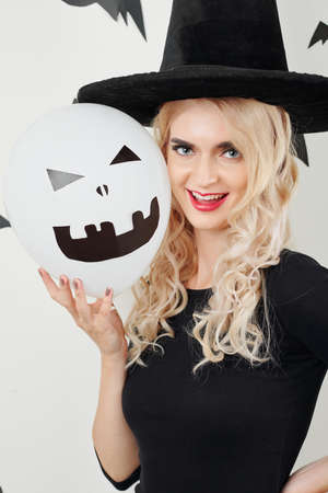 Cheerful young sorceress in pointy hat holding baloon with creepy face and smiling at camera